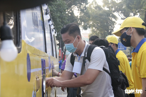 A man gets his hands sanitized before getting face masks for free from the bus at the Ho Chi Minh City Youth Culture House in District 1